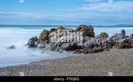 Eine lange Aufnahme des Meeres waschen in um Felsen von Porth Nobla, Rhosneigr auf der Isle of Anglesey. - Stockfoto