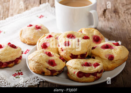 Englisch Wandleuchten Kekse mit roten Johannisbeeren sind mit Kaffee und Milch in der Nähe serviert - auf den Tisch. Horizontale - Stockfoto