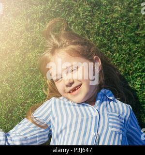Kleines Mädchen mit Kamera, lächelnd und liegen auf dem Rasen. Sommer Freizeitaktivitäten. Mädchen ohne vorderen Zähne. - Stockfoto