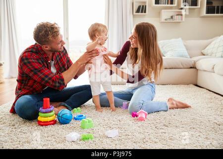 Junges Paar helfen toddler Tochter stehen im Wohnzimmer - Stockfoto