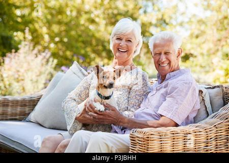 Gerne älteres Paar mit einem Haustier Hund im Garten - Stockfoto