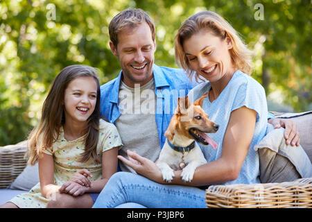 Eltern und Tochter sitzen mit ihrem Hund im Garten - Stockfoto