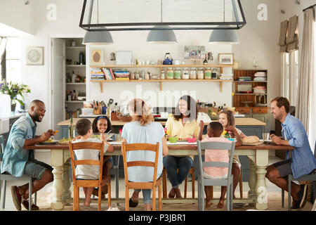 Zwei Familien Mittagessen gemeinsam in der Küche zu Hause. - Stockfoto