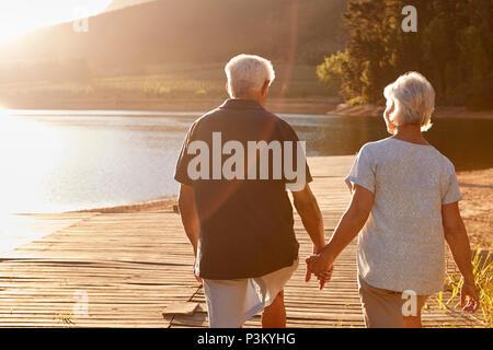 Romantische Senior Paar auf hölzernen Steg am See - Stockfoto