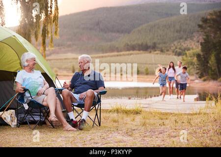 Multi-Generation Familie auf Campen am See zusammen - Stockfoto