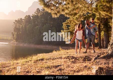 Eltern geben Kindern Piggyback Rides auf Spaziergang am See - Stockfoto