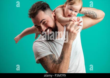 Verspielt Vater sein lächelndes Kind an Hals über blauer Hintergrund - Stockfoto