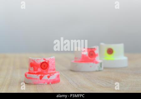 Mehrere Düsen aus Kunststoff Farbe mit einer Feldspritze, die auf einer hölzernen Oberfläche gegen eine graue Wand Hintergrund liegen. Die Kappen sind in fluoreszierenden Farbe verschmiert. T - Stockfoto