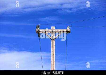 Konzeptionelle Bild der Telefonmast und Drähte vor blauem Himmel ...