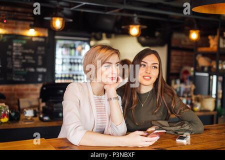 Zwei attraktive junge Freundinnen plaudern auf dem Smartphone im Cafe - Stockfoto