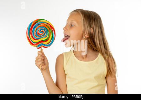 Nettes glückliches Kind mit Süßigkeiten Lutscher, glückliches Mädchen mit grossen Zucker Lutscher, Kid essen Süßigkeiten. Überrascht Kind mit Süßigkeiten. auf weißem Hintergrund, - Stockfoto