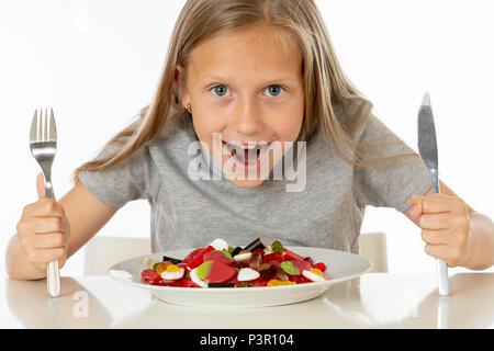 Lustige Happy girl mit Platte von Süßigkeiten Lutscher am Stiel glückliche kleine Mädchen mit großen kandiszucker am Stiel kind Süßigkeiten essen. Überrascht Kind mit Süßigkeiten. iso - Stockfoto
