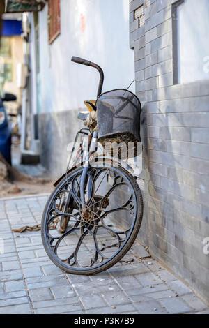 Peking, China - MÄRZ 10, 2016: Fahrräder, Roller und Autos in Peking Straßen. Ein altes Fahrrad wird an der Wand des Hauses platziert. - Stockfoto
