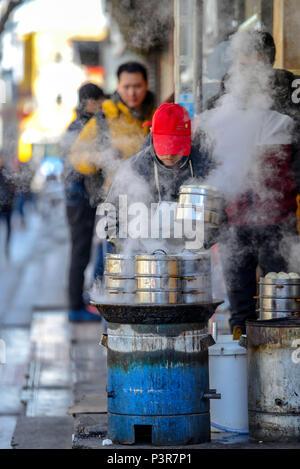 Peking, China - MÄRZ 10, 2016: Kaufleute kochen Lebensmittel direkt auf der Straße vor den Augen. - Stockfoto