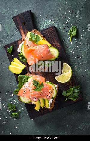 Sandwich oder Toast. Korn Brot mit Lachs, weißer Käse, Avocado, Gurke und Spinat. Ansicht von oben am Tisch aus Stein. Gesunde Snacks, gesunde Fette und - Stockfoto