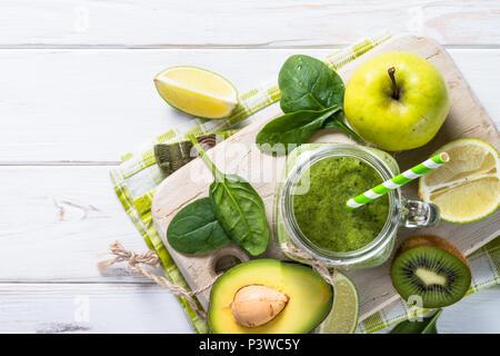Grüne Smoothie und Zutaten. Kalk, Apfel, Spinat, Kiwi, Avocado. Ansicht von oben auf die weiße Holztisch - Stockfoto