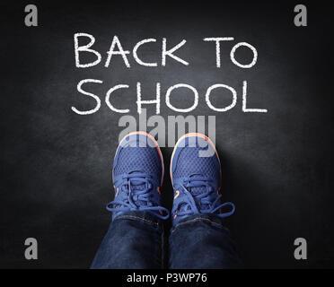 Zurück zu Kind die Schule in Turnschuhen neben Kreide auf Tafel stehend - Stockfoto
