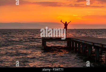 Frau, die gegen den Sonnenuntergang am Pier - Stockfoto