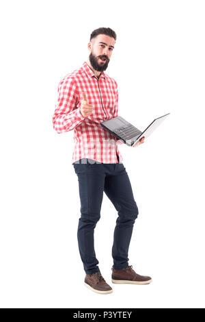 Erfolgreiche junge Bartgeier hipster Geschäftsmann auf Laptop zeigt mit dem Finger auf sie. Voller Körper auf weißem Hintergrund. - Stockfoto