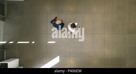 Zwei Geschäftsleute gehen im Büro Flur und sprechen. Blick von oben auf die Geschäftsmann und Frau in Bürogebäude Lobby. - Stockfoto