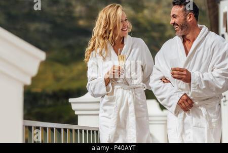 Liebende Paar in Bademantel gehen auf dem Balkon mit einem Glas Wein und ein Lächeln auf den Lippen. Mann und Frau tragen Bademäntel in Ihrer Luxuriösen Villa. - Stockfoto