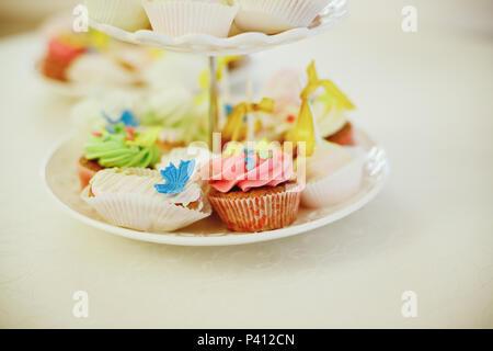 Gourmet Cupcakes mit bunten buttercream frosting auf weißer Tisch. Urlaub Bild, festliche Bäckerei. Getönten Bild. Frische hausgemachte Muffins. Dekorative Geburtstag cupcaces auf Kuchen stand. Kopieren Sie Platz - Stockfoto
