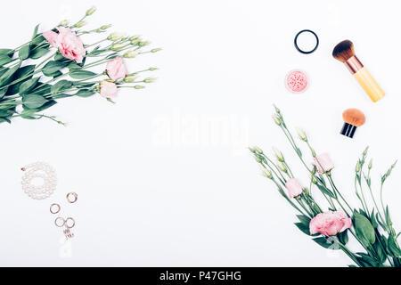 Rahmen des dekorativen Frauen Kosmetik und Schmuck mit eustoma Blumen, Ansicht von oben. Flach Blumenschmuck auf weißem Hintergrund. - Stockfoto