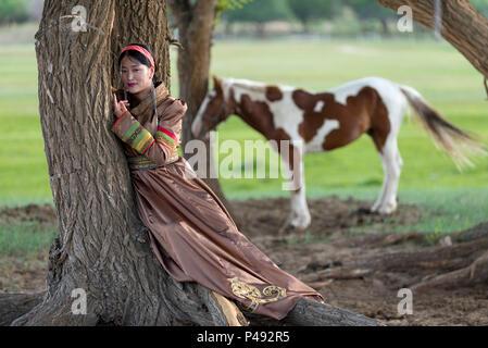 Frau, die traditionelle mongolische Kostüm entspannt sich mit Pferd im Sommer Camp, Xilinhot, der Inneren Mongolei, China - Stockfoto
