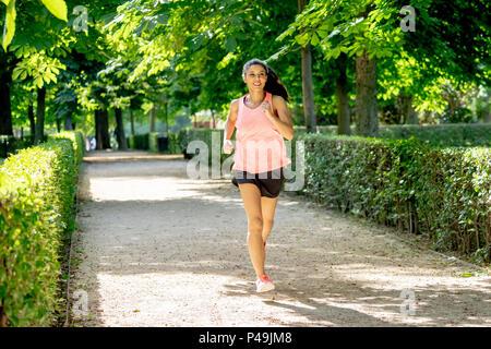 Junge attraktive und Happy runner Frau im Herbst Sportbekleidung Running und Training auf Joggen im Freien Training im City Park mit Bäumen und Gelb lassen - Stockfoto