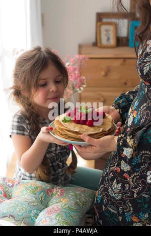 Mom und das Mädchen halten einen Teller mit hausgemachten Pfannkuchen und Beeren. Köstliches Frühstück zu Hause. Eine glückliche Familie. Guten Morgen. - Stockfoto