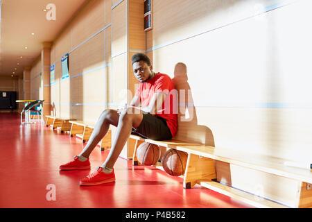 Schwarze Basketballspieler ruht auf der Werkbank - Stockfoto