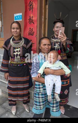 Familie mit mehreren Generationen in traditionellen Kostümen & silberne Halsketten, Yao, die ethnischen Minderheiten angehören, Dorf, Maolan Lu, Libo, Provinz Quizhou, China - Stockfoto