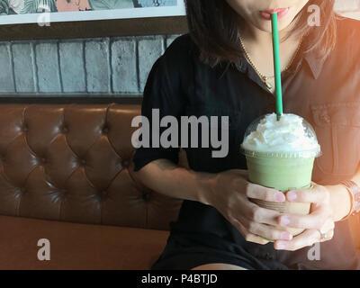 Asian Business Frau trinken grünen Tee frappe, gerade im Cafe am Morgen entspannen. - Stockfoto