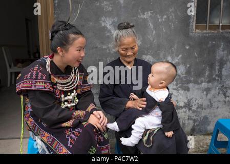 Mutter, Baby und Großmutter gekleidet in traditionellen Kostümen, Yao, die ethnischen Minderheiten angehören, Dorf, Libo, Provinz Guizhou, China - Stockfoto