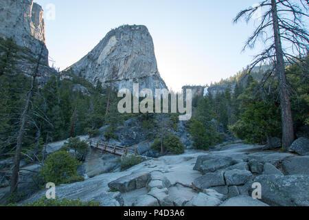 Liberty Cap rock Formation und Nevada fällt im Hintergrund aus dem Nebel Wanderweg gesehen und Brücke über den Merced River im Yosemite National Pa - Stockfoto