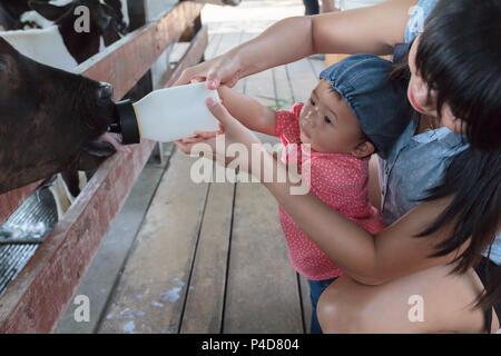Asiatische schöne Mutter kümmern ihre niedlichen New Born Baby füttern Milch für das Baby Kuh in der Farm, Aktivitäten Familie lernen erleben zu verbessern - Stockfoto