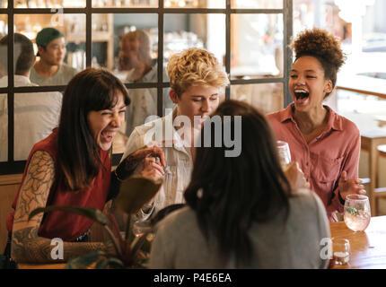 Vielfältige Gruppe von Freundinnen zusammen lachen in eine trendige Bar - Stockfoto