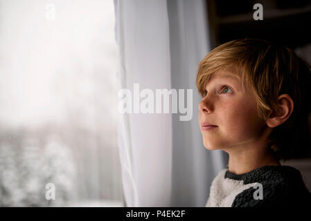 Junge Blick aus dem Fenster im Winter - Stockfoto