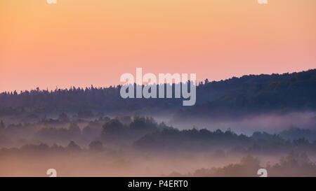 Nebligen Morgen des hügeligen Gegend mit Lichtstrahl. - Stockfoto