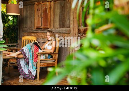 Attraktives Mädchen sitzen auf der Veranda des Bungalows mit tropischem Gartenblick, Romanze in Papier Buch lesen. Junge Frau, die sich in Luxus Villa - Stockfoto