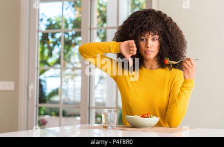Afrikanische amerikanische Frau essen Pasta Salat mit Verärgerten Gesicht, negatives Vorzeichen zeigen Abneigung mit Daumen nach unten, Ablehnung Konzept - Stockfoto