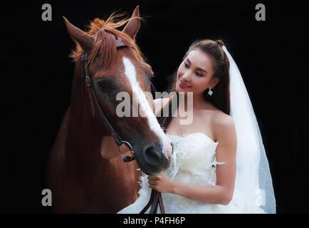 Junge schöne Schönheit Braut fashion White Wedding Kostüm stehen mit den stattlichen Pferd auf schwarzem Hintergrund - Stockfoto