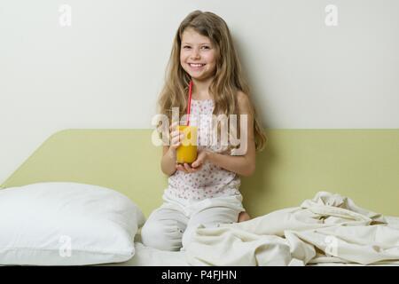 Schläfrige Mädchen von 7 Jahren im Schlafanzug, sitzt im Bett zu Hause und Getränke Orangensaft. - Stockfoto