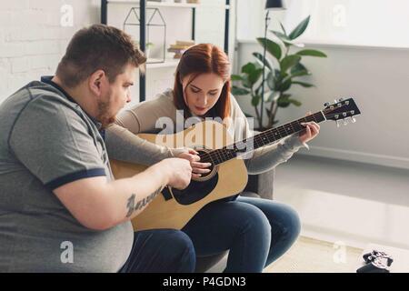Freund lehre Freundin spielen akustische Gitarre zu Hause - Stockfoto