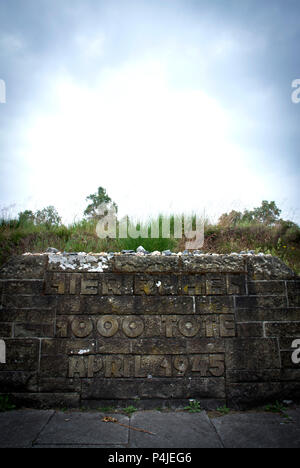 Eine Markierung Stein und verwitterte Inschrift des einen der 13 Hügel, dass Mark die Massengräber, in denen die Opfer des Lagers Bergen-Belsen begraben sind. - Stockfoto