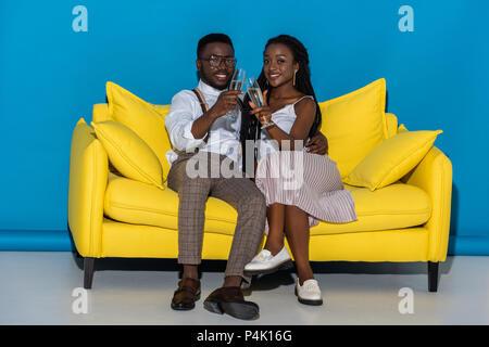 Schöne afrikanische amerikanische Paar hält Gläser Wein und lächelt in die Kamera während der Sitzung auf Gelb couch - Stockfoto