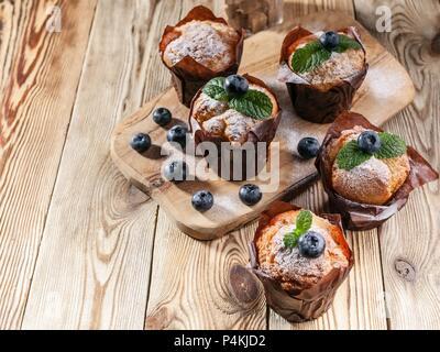 Muffins mit Heidelbeeren auf einer hölzernen Hintergrund. hausgemachte Backen - Stockfoto
