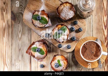 Muffins mit Heidelbeeren und eine Tasse heiße Schokolade auf einem hölzernen Hintergrund. Hausgemachte backen. Ansicht von oben Stockfoto