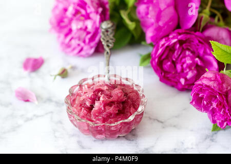Jam mit Rosenblätter in eine Glasschüssel und hellen Rosen auf einem hellen Hintergrund. Selektive konzentrieren. - Stockfoto