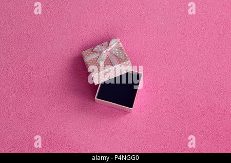 Offenes kleines Geschenk Box in Rosa mit einer kleinen Verbeugung liegt auf einer Decke aus weichem, flauschigen Rosa fleece Stoff. Verpackung für ein Geschenk für Ihre schönen girlfrien - Stockfoto